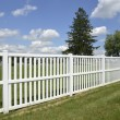 White vinyl fence by green lawn — Stock Photo