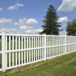 Stock Photo: White vinyl fence by green lawn