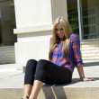 Female teenager sitting on concrete steps — Stock Photo