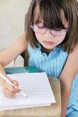 Criança sentada na mesa de escola com óculos — Fotografia Stock