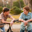 Two happy teenage boys talk in the park while resting on their bicycles — Stock Photo #10757118