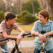 Two happy teenage boys talk in the park while resting on their bicycles — Stock Photo