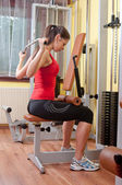 Beautiful girl exercising her back muscles in the gym — Stock Photo