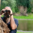 Bald man watching the nature through binoculars while leaning on old tree — Stock Photo