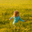 Cute happy girl running in the field of wheat on sunny spring day — Stock Photo