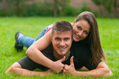 Young couple in love lying on the grass and showing thumbs up — Stock Photo