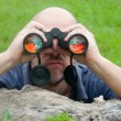 Bald man watching the nature through binoculars while leaning on old tree - Stock Photo