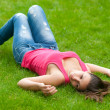 Beautiful girl lying on the grass on calm spring day — Stock Photo #11015034
