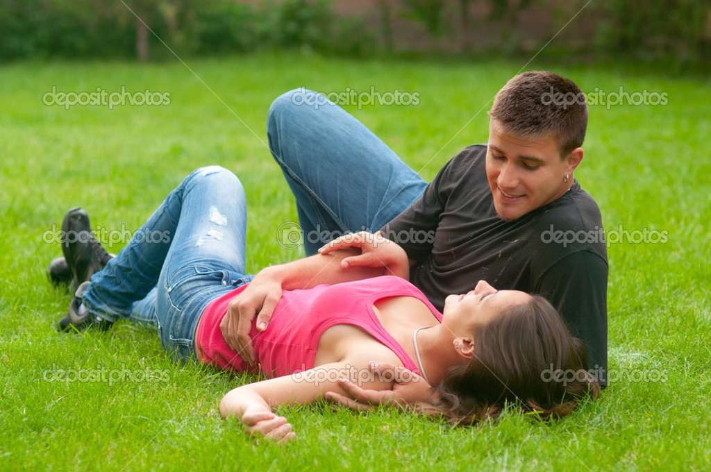 Young couple in love lying on the grass and looking at each other — Stock Photo #11015075