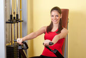Beautiful young girl exercising in the gym — Stock Photo