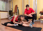 Beautiful young girl doing stretching exercises in the gym under supervision of her coach — Stock Photo