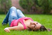 Hermosa niña sonriente tirado en el césped en primavera calma — Foto de Stock