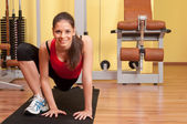 Beautiful young woman exercising in the gym on the floor — Foto Stock