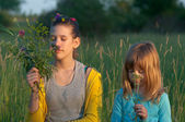 Teenage girl and little girl smelling flowers picked up at the meadow — Stock Photo