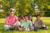 Happy teenage friends spending time together in the park on sunny summer day — Stock Photo