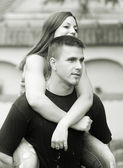 Young happy couple piggy back riding outdoor - monochrome photo — Stock Photo