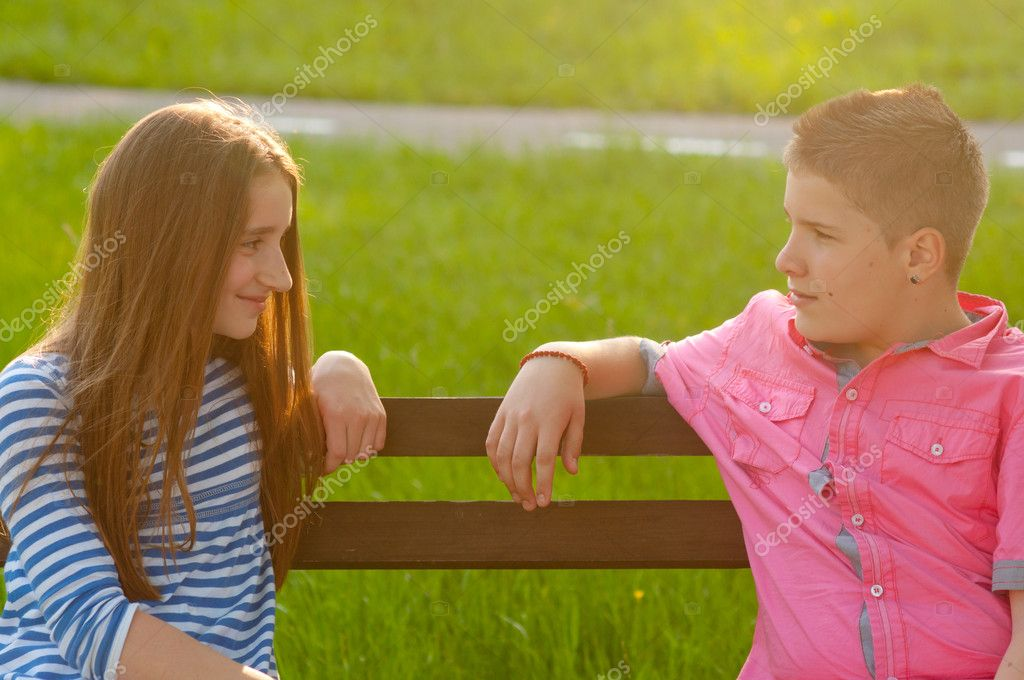 Happy boy and a girl sitting on the bench and looking at each other on sunny spring day — Stock Photo #11258503