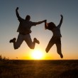 Young happy couple jumping high in the air on sunny summer day — Stock Photo