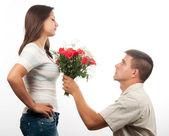 Bağışlanmak için yalvaran ve gül buketi kız arkadaşına sunan yakışıklı delikanlı — Stok fotoğraf