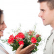 Man giving bouquet of flowers to his girlfriend isolated on white — Stock Photo