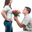 Stock Photo: Handsome young man pleading for forgiveness and offering bouquet of roses to his girlfriend