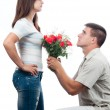 Handsome young man pleading for forgiveness and offering bouquet of roses to his girlfriend — Stock Photo #11456710