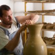 Craftsman making vase from fresh wet clay on pottery wheel — Stock Photo #11456718