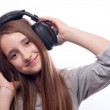 Beautiful teenage girl listens to music through the headphones — Stock Photo