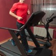 Stock Photo: Young handsome mrunning on treadmill in home made gym