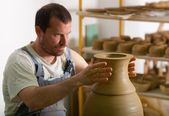Craftsman making vase from fresh wet clay on pottery wheel. Focus on hands — Stock Photo