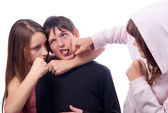 Two teenage girls beating teenage boy isolated on white — Stock Photo
