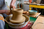 Craftsman making vase on the pottery wheel in pottery workshop — Stock Photo