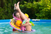Two teenage girls having fun in the home swimming pool with their childhood toys — Stock Photo