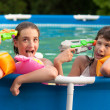 Two teenage girls having fun with their childhood toys in the home pool — Stock Photo #11543546