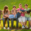 Stock Photo: Five teenage boys and girls having fun in the park on sunny spring day