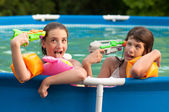 Two teenage girls having fun with their childhood toys in the home pool — Stock Photo