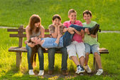Five teenage boys and girls having fun in the park on sunny spring day — Stock Photo