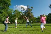 Tiener jongens en meisjes spelen met de bal in het park op zonnige lentedag — Stockfoto