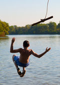 Teenage boy jumping in the river from the swinging rope on sunny summer day — Stock Photo