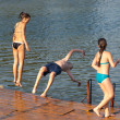 Teenage boy and teenage girls jumping into the river from old dock — Stock Photo