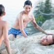 Two teenage boys covering with sand teenage girl on river beach — Stock Photo