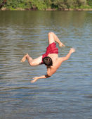 Teenage boy jumping in the river on sunny summer day — Stock Photo