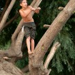 Teenage boy jumping into the river from the rope hanging from the tree — Stock Photo #11755222
