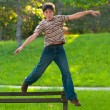 Happy teenage boy jumping from the bench in the park — Stock Photo #11755323