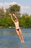 Cute teenage girl jumping into the river from the swinging rope on sunny summer day — Stock Photo