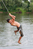 Teenage boy jumping into the river from the swinging rope — Stock Photo
