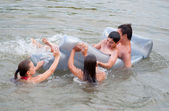 Teenage boys and girls having fun with a mattress in the river — Stock Photo
