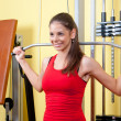 Stock Photo: Beautiful girl exercising her back muscles in gym
