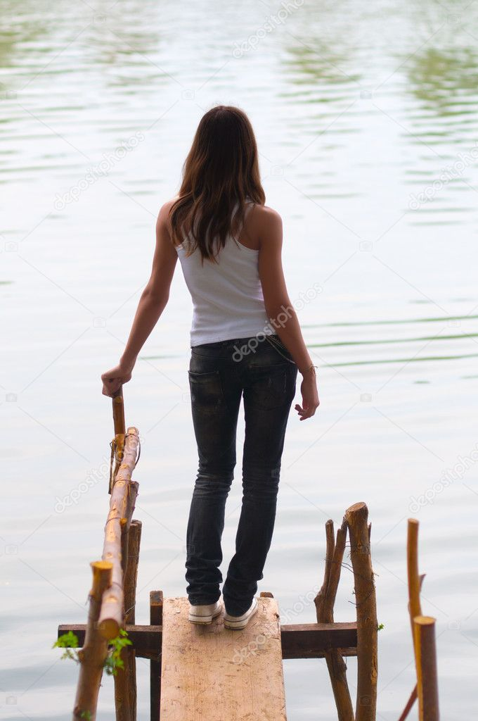 Beautiful lonely teenage girl standing on the edge of the river ...