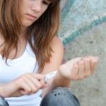 ������, ������: Pretty depressed teenage girl preparing to cut her wrists open